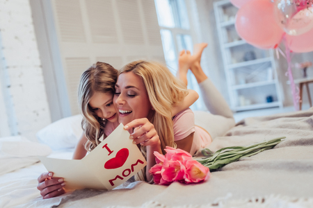 I love you, mom! Attractive young woman with little cute girl are spending time together at home while lying on bed. Mom is receiving presents from daughter on Mother's Day. Happy family concept.