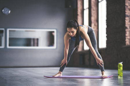 Attractive young sport girl is doing yoga in light room. Healthy lifestyle concept.