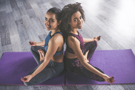 Two attractive young sport girls are doing yoga together. Group training. Healthy lifestyle concept.