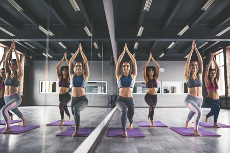 Attractive young sport girls are doing yoga together. Group training. Healthy lifestyle concept.