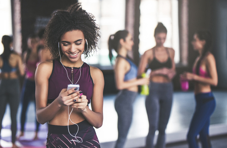 Attractive sport girls are having rest after doing yoga together. Healthy lifestyle concept. Young Afro-American woman is standing on the foreground with smart phone in hands and listening to music. 스톡 콘텐츠