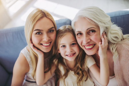 Little cute girl, her attractive young mother and charming grandmother are spending time together at home. Womens generation. International Womens Day. Happy Mothers Day.