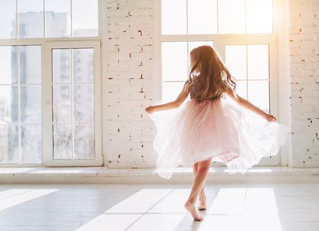 美しいドレスのかわいい少女は、明るい日当たりの良い部屋で踊っています