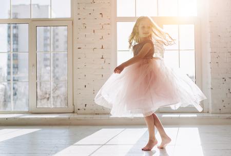 Śliczna mała dziewczynka w pięknej sukience tańczy w świetle słonecznym pokoju Zdjęcie Seryjne