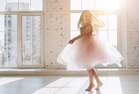 Cute little girl in beautiful dress is dancing at light sunny room