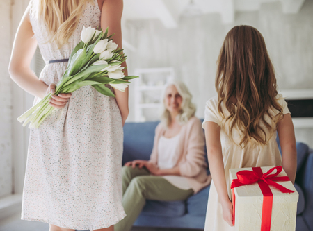 Little cute girl, her attractive young mother and charming grandmother are spending time together at home. Giving presents. Women's generation. International Women's Day. Happy Mother's Day. Stok Fotoğraf