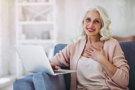 Attractive mature woman is sitting on sofa at home with laptop. Stock Photo