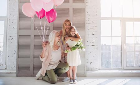 Klein schattig meisje, haar aantrekkelijke jonge moeder en charmante grootmoeder staan met luchtballonnen en bloemen in lichte kamer. Dames generatie. Internationale Vrouwendag. Gelukkige Moederdag.
