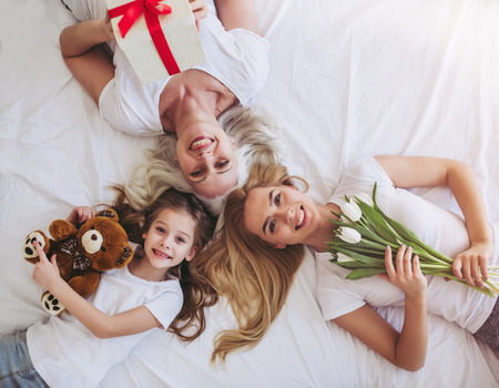 Top view of little girl, her attractive young mother and charming grandmother are lying on bed while spending time together at home. Women's generation. International Women's Day. Happy Mother's Day.
