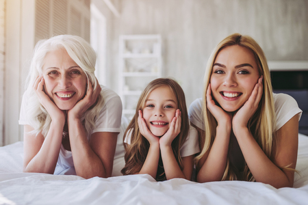 Little cute girl, her attractive young mother and charming grandmother are lying on bed and spending time together at home. Women's generation. International Women's Day. Happy Mother's Day. Archivio Fotografico