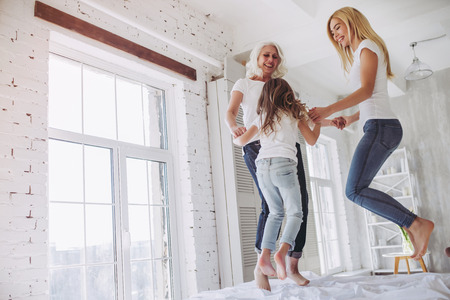 Little girl, her attractive mother and charming grandmother are having fun and jumping on bed while spending time together at home. Women's generation. International Women's Day. Happy Mother's Day.