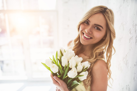 Portrait of attractive young woman with tulips is standing in light room and smiling. Happy international womens day! Celebrating 8th of March. Stock Photo
