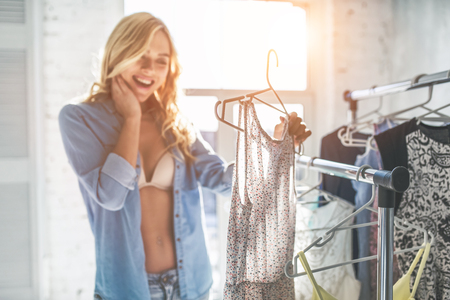 Attractive young woman is choosing clothes in light room. Girl in wardrobe. Stock Photo