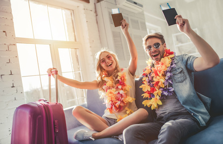 Young romantic couple wearing Hawaii accessories and sunglasses is preparing for travel at home. Sitting on sofa with passports and tickets in hands while suitcases are standing nearby