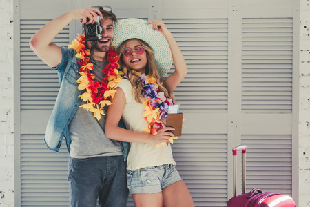 Young romantic couple is preparing for traveling. Standing on grey background in Hawaii accessories, sunglasses and hat with passport and ticket in hand. Suitcases are nearby. 版權商用圖片