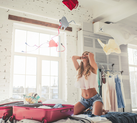 Attractive young woman is preparing for traveling while sitting on bed with big suitcase and scattering clothes up in the air. Having fun at home.