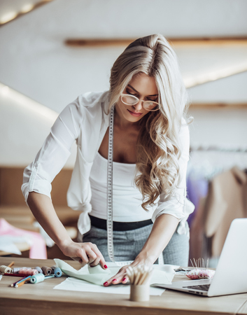 Attractive female fashion designer is working in her workshop. Stylish woman in process of creating new clothes collection. Stock Photo - 96131574