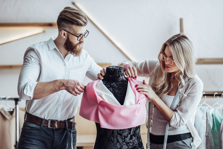 Couple of fashion designers are working in workshop. Attractive young woman and stylish bearded man are in process of creating new clothes collection. Imagens