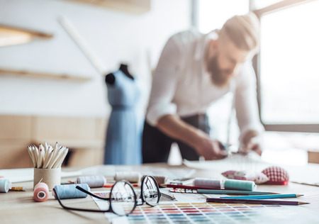 Handsome male fashion designer is working in his workshop. Stylish bearded man in process of creating new clothes collection. Stockfoto