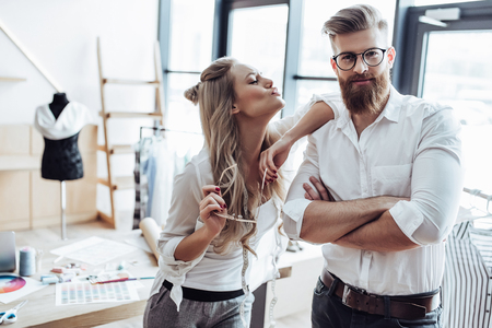 Couple of fashion designers are working in workshop. Attractive young woman and stylish bearded man are in process of creating new clothes collection. Stock Photo