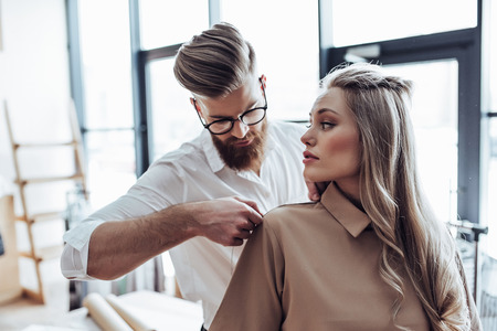 Handsome male fashion designer is taking measurements from attractive female model while working in his workshop. Stylish bearded man in process of creating new clothes collection.