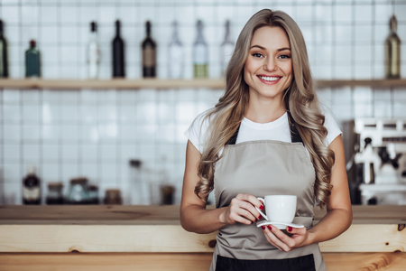 Beautiful female barista is working in coffee shop. Attractive young woman is standing  behind the bar counter, making coffee and welcomes customers.
