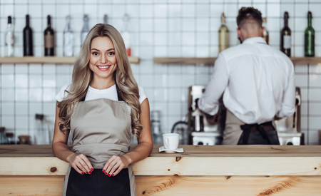 Couple of barista are working in coffee shop. Attractive young woman and handsome bearded man are standing together behind the bar counter Imagens