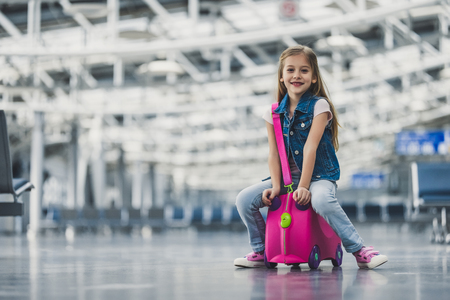 Little cute girl is sitting on her pink suitcase in airport terminal. Ready for traveling and new adventures! Banco de Imagens