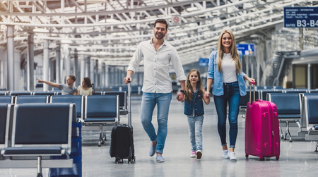 Family in airport. Attractive young woman, handsome man and their cute little daughter are ready for traveling! Happy family concept. Stok Fotoğraf