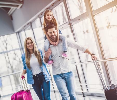 空港の家族。魅力的な若い女性、ハンサムな男と彼らのかわいい娘は旅行の準備ができています!幸せな家族のコンセプト。
