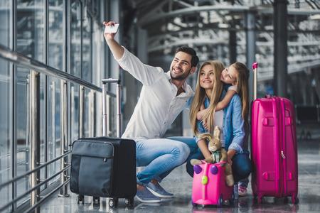 Familie im Flughafen. Attraktive junge Frau, gutaussehender Mann und ihre süße kleine Tochter sind bereit zum Reisen! Happy Family-Konzept.