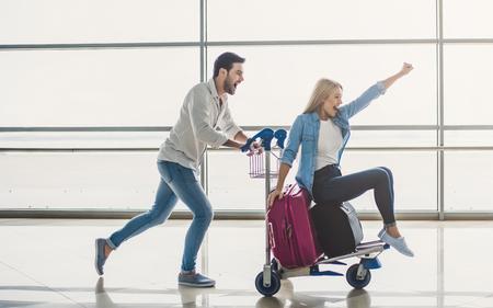 Couple romantique à l'aéroport. Belle jeune femme et bel homme avec des valises sont prêts à voyager. S'amuser sur le chariot à bagages en attendant le départ. Banque d'images - 96718869