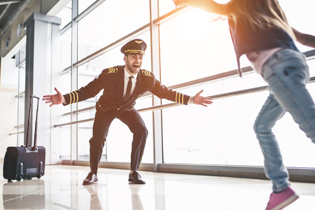 I missed you, dad! Handsome young male pilot in uniform is meeting his little cute daughter in airport terminal. Stock Photo