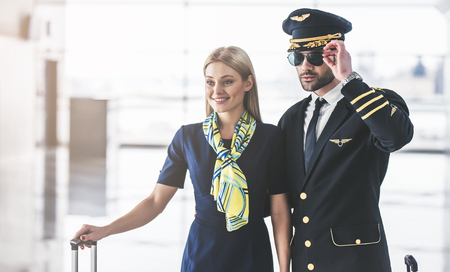 Handsome male pilot and attractive female flight attendant are standing in airport terminal together. Foto de archivo