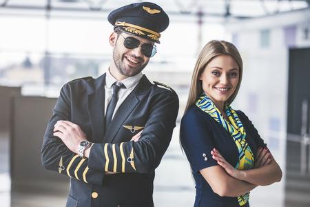 ハンサムな男性パイロットと魅力的な女性客室乗務員が一緒に空港ターミナルに立っています。