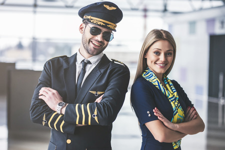 Handsome male pilot and attractive female flight attendant are standing in airport terminal together. Archivio Fotografico