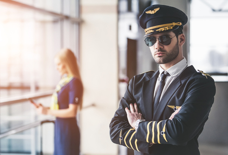Handsome male pilot and attractive female flight attendant are standing in airport terminal together. Zdjęcie Seryjne