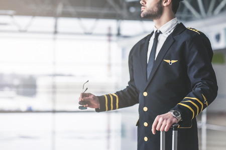 Cropped image of handsome young male pilot in the airport terminal. Banque d'images
