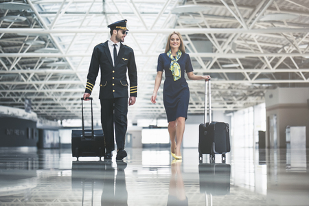 Handsome male pilot and attractive female flight attendant are walking in airport terminal together.