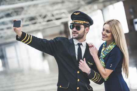 Handsome male pilot and attractive female flight attendant are standing in airport terminal together and making selfie on a smart phone.