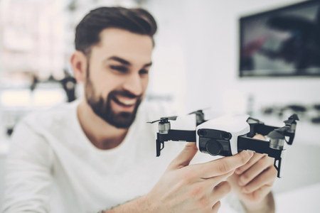 Handsome young man in modern light quadcopter store. Choosing the appropriate drone