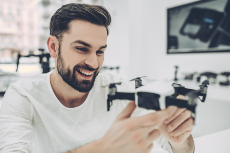 Handsome young man in modern light quadcopter store. Choosing the appropriate drone Stock Photo - 96718998