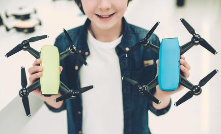 Cute little boy in modern light quadcopter store.