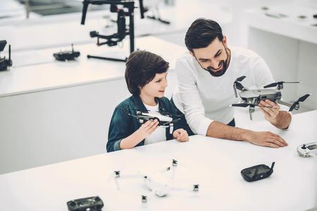 ハンサムな若者と彼のかわいい息子は、現代の軽いクワッドコプター店にあります。適切なドローンの選択 写真素材