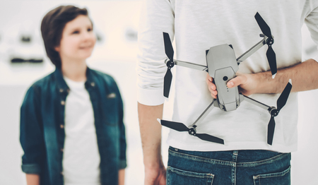 Handsome young man and his cute son are in modern light quadcopter store. Dad giving present to his son. Stock Photo
