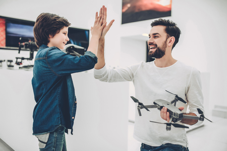 Handsome young man and his cute son are in modern light quadcopter store. Choosing the appropriate drone and giving five to each other Stock Photo