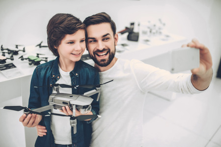 Handsome young man and his cute son are in modern light quadcopter store. Choosing the appropriate drone and making selfie on a smart phone.