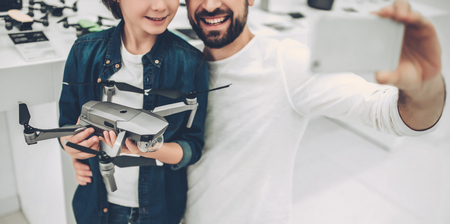 Cropped image of handsome young man and his cute son are in modern light quadcopter store. Choosing the appropriate drone and making selfie on a smart phone.