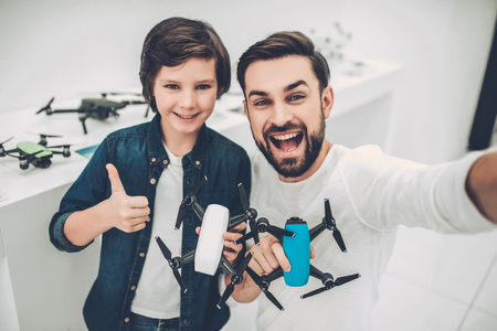 Handsome young man and his cute son are in modern light quadcopter store. Choosing the appropriate drone and making selfie.