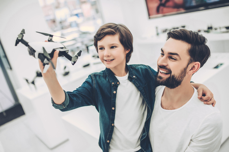 Handsome young man and his cute son are in modern light quadcopter store. Choosing the appropriate drone Stock Photo - 96719095